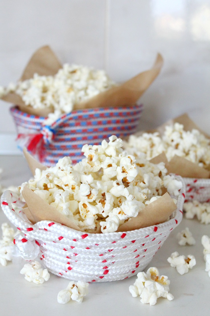 Rope bowl holding cooked popcorn wrapped in parchment paper