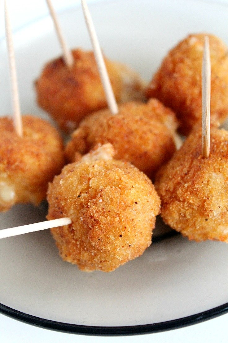 Spicy fried cheese balls on a white plate, with toothpicks for easy serving
