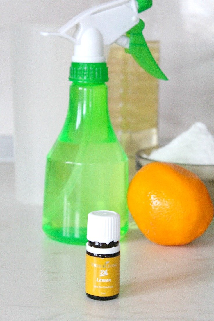 Image of homemade natural disinfectant for home in a green spray bottle, next to a bottle of essential oils and lemon fruit