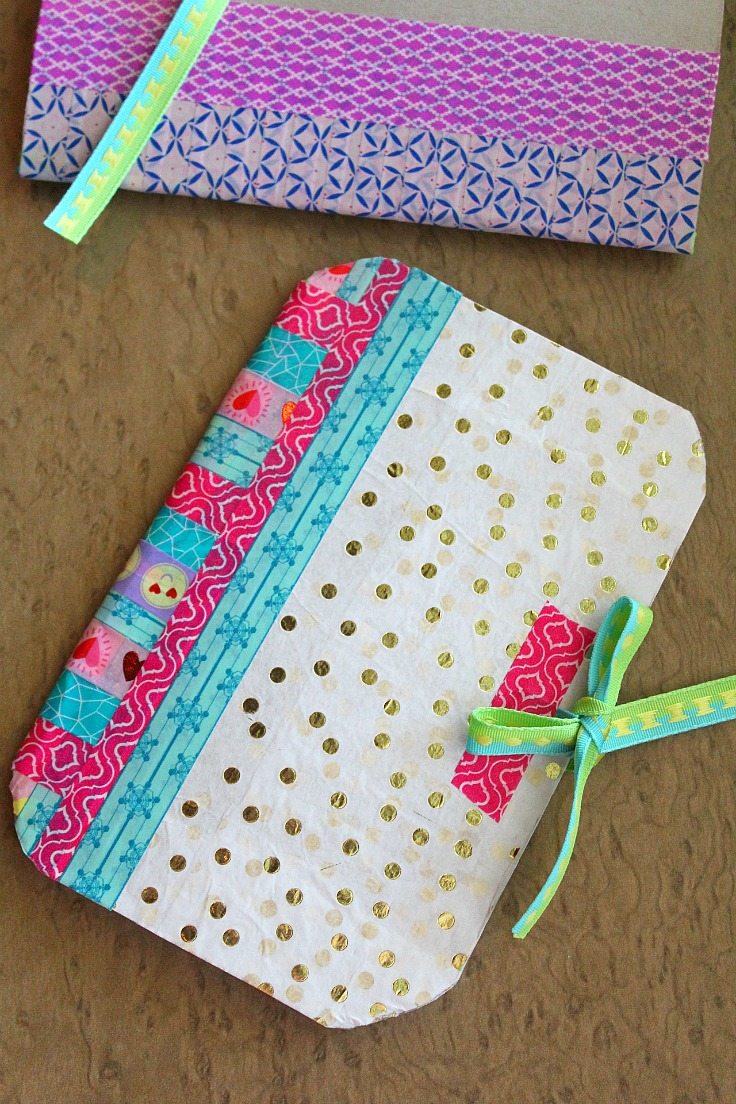 DIY notebook made with cereal box, tissue paper in gold polka dots, washi tape in various colors and ribbon