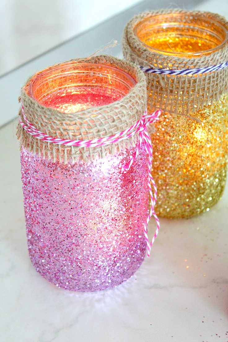 Mason Jar Luminaries made out of jars painted in mod podge and glitter and decorated with twine ribbon and bakers twine around the neck