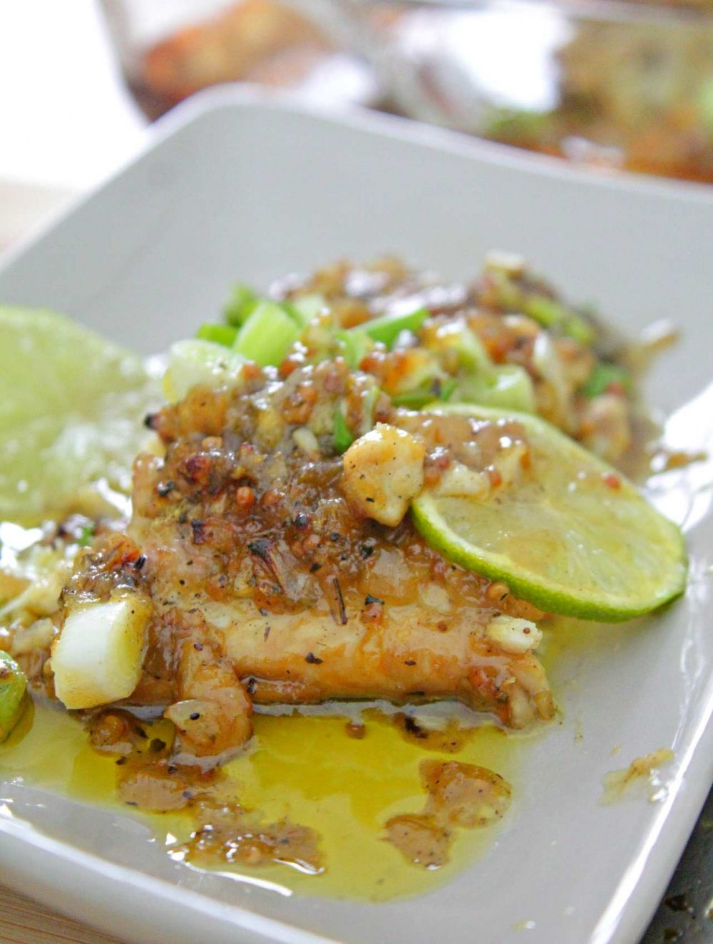Honey mustard fish on a white serving plate with a slice of lime and garlic