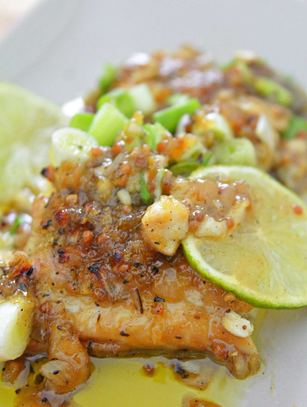 Baked fish in honey mustard sauce for fish sprinkled with green onions and served o a white plate with slices of lime