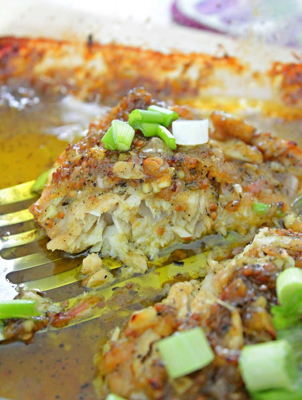 Fish with mustard sauce in a baking dish, on a turner, sprinkled with green onions