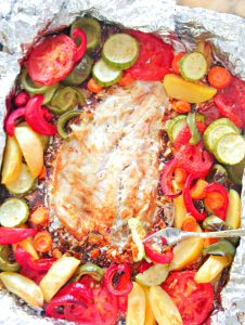 Fish that is baked in the oven in aluminium foil, together with vegetables, garlic and lemon juice