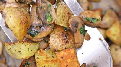 Roasted potatoes and mushrooms with garlic and fresh parsley in a baking sheet