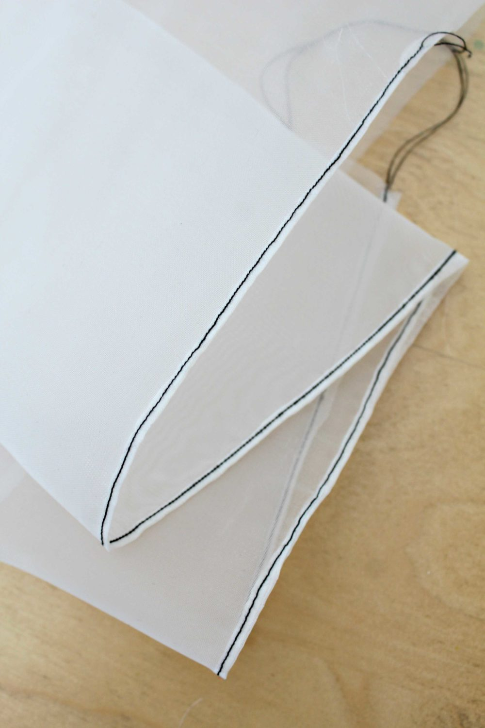 Piece of fabric with a rolled hem showing how to sew a rolled hem