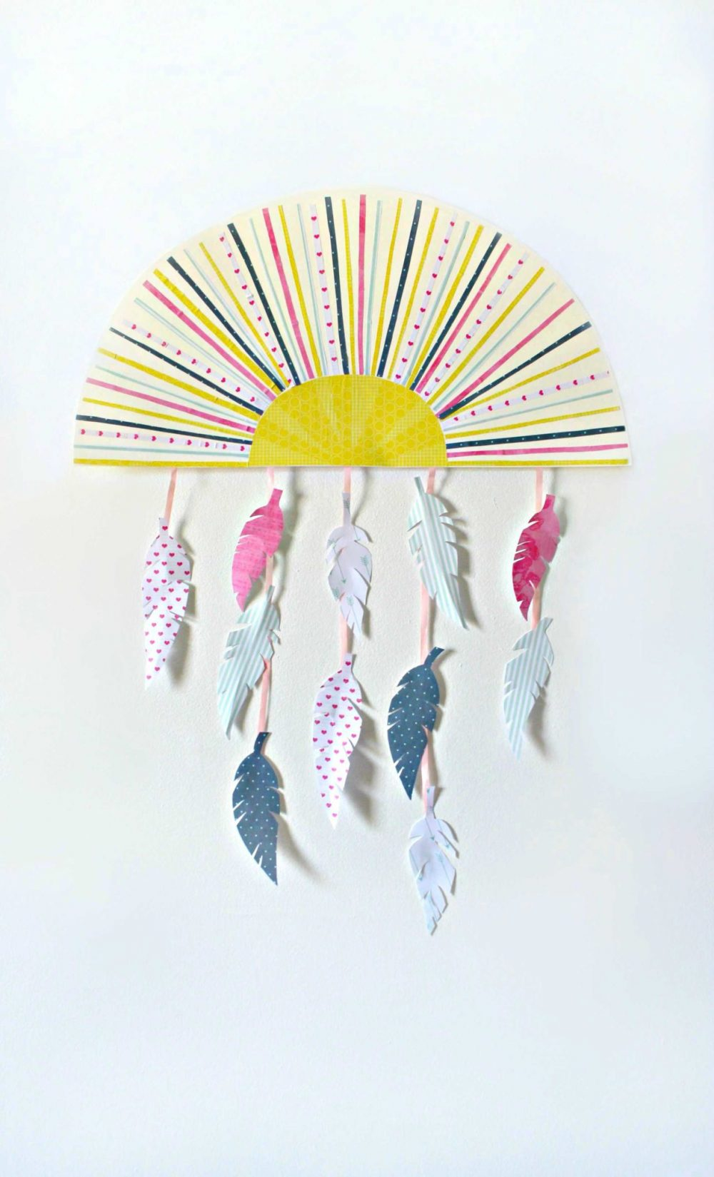 Feather wall decor in the shape of a half sun with hanging feathers