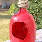 Plastic bottle bird feeder made out of pop bottle, painted in red with twine and an artificial leaf attached to the neck