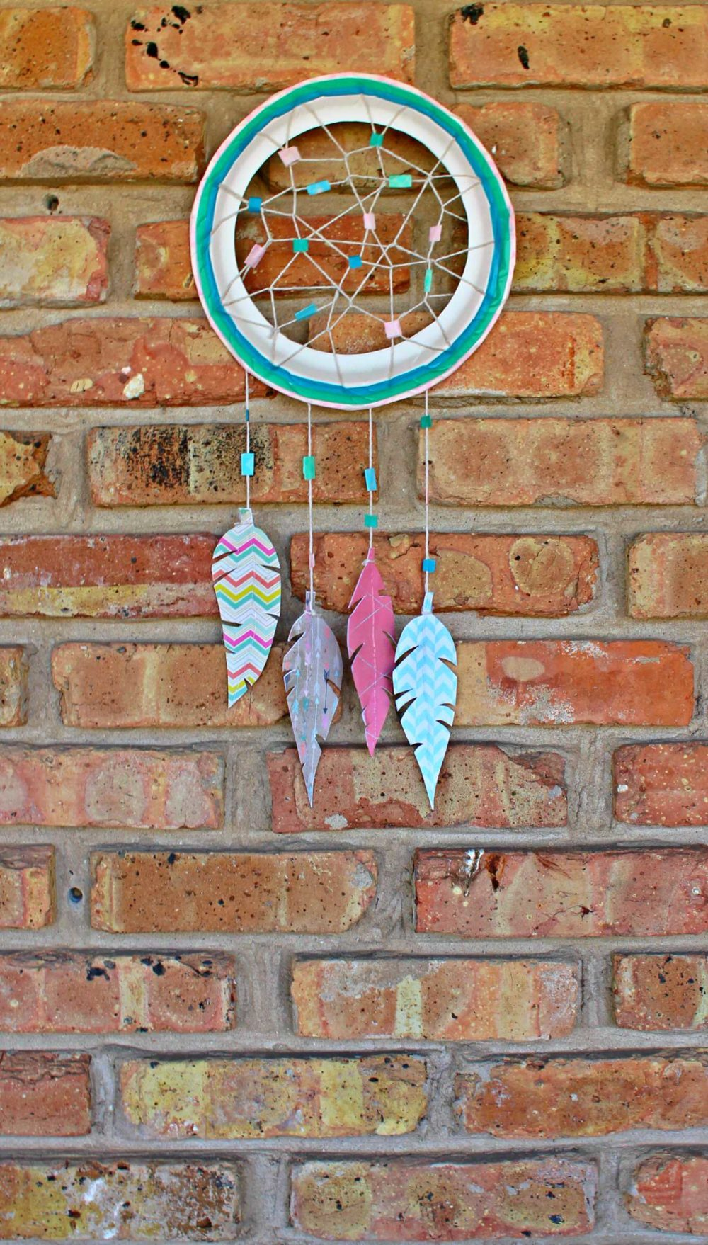 Paper dream catcher made with paper feathers, twine and washi tape and displayed on a wall