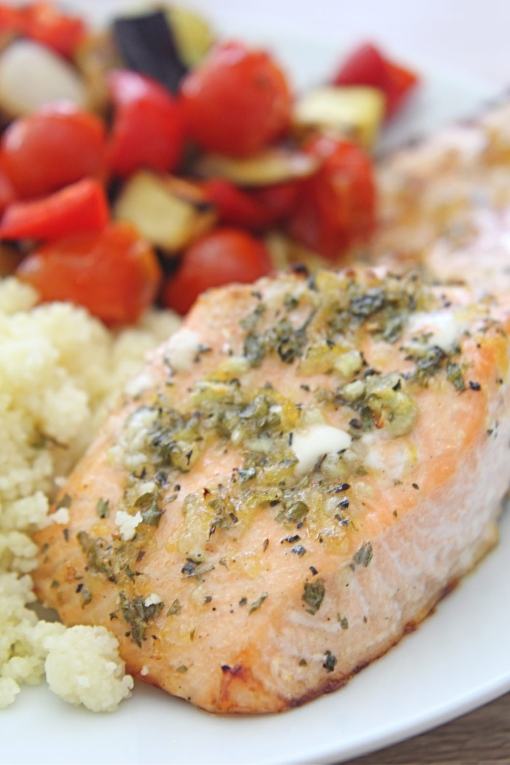 Lemon herb salmon with roasted vegetables and couscous on a white serving plate
