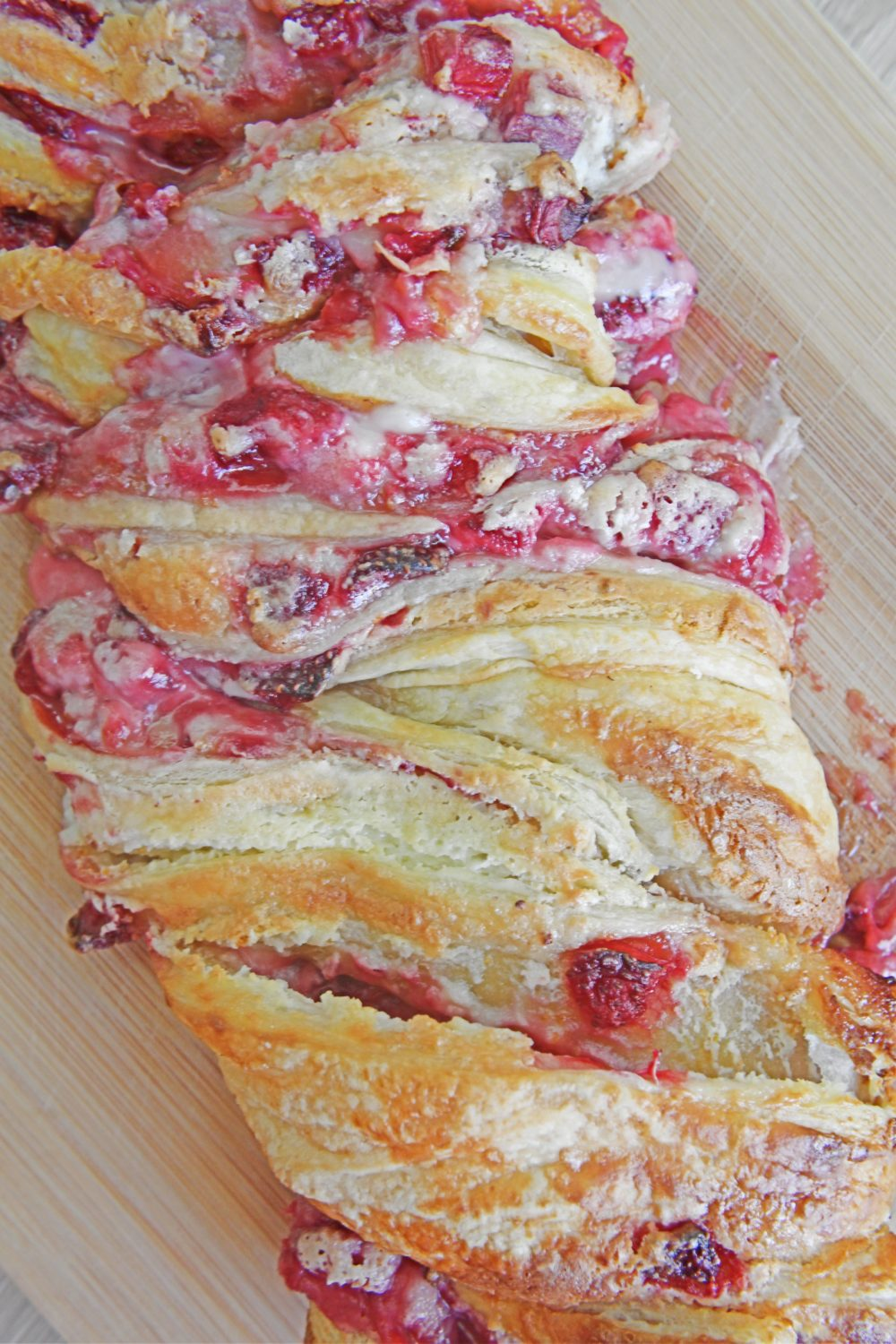 Strawberry puff pastry braid with cream cheese, on a cutting board