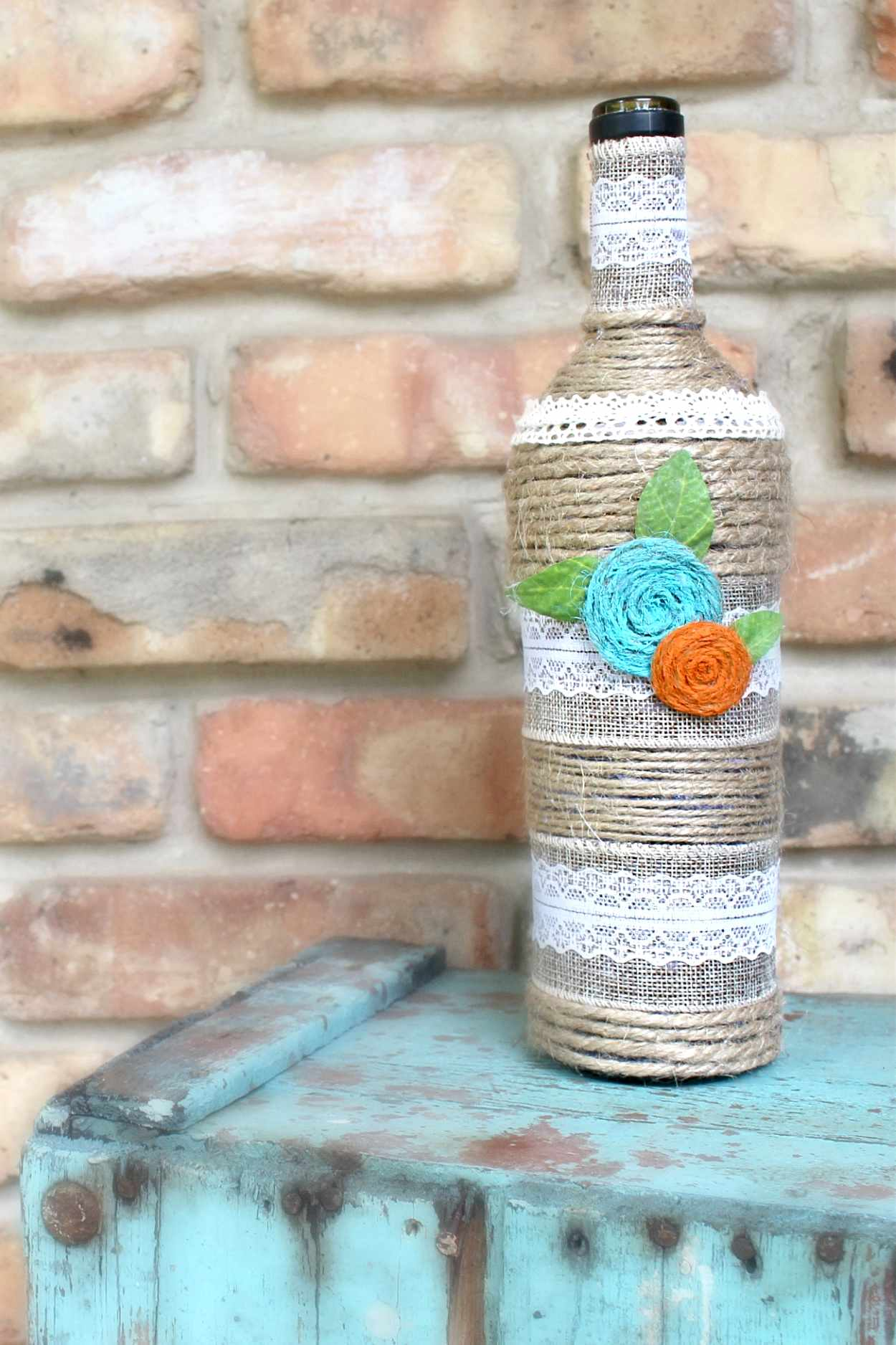 Wine bottle art made with recycled wine bottle, twine, lace and paint