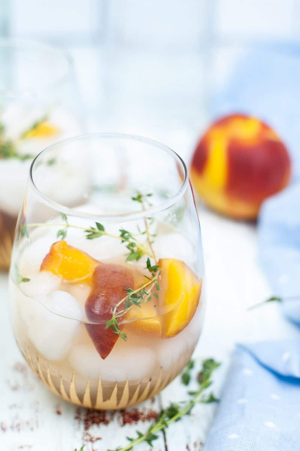 Peach gin cocktail in a glass dressed with peach wedges and thyme sprigs
