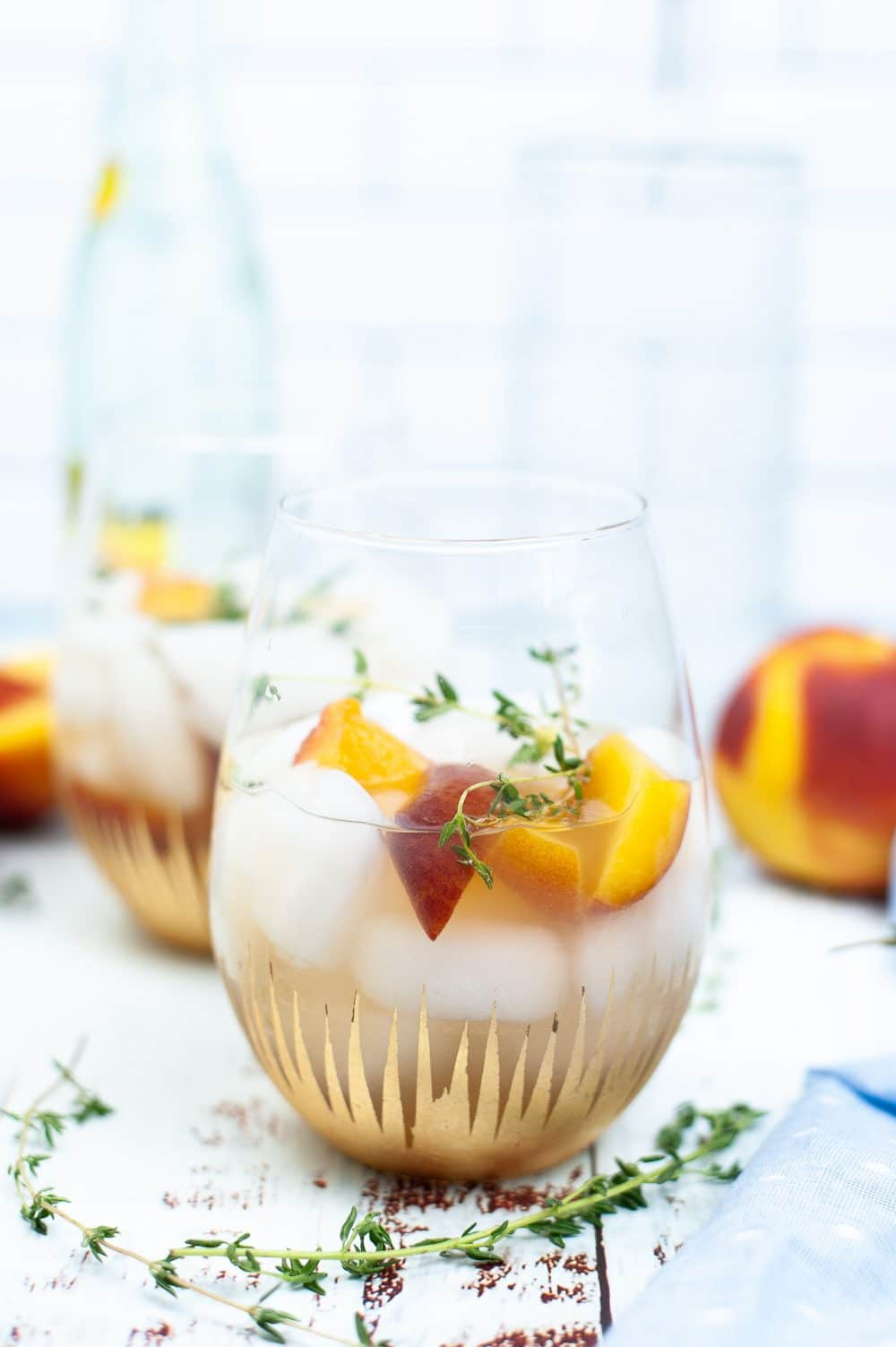 Peach syrup cocktail in a glass dressed with slices of peaches and thyme sprigs