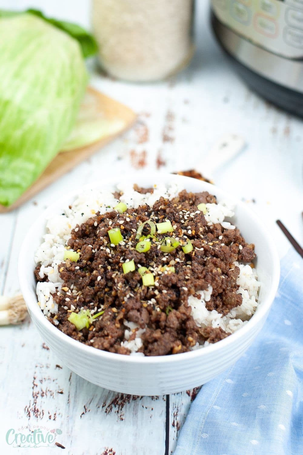 Image of Korean beef and rice recipe served in a white bowl next to an Instant Pot
