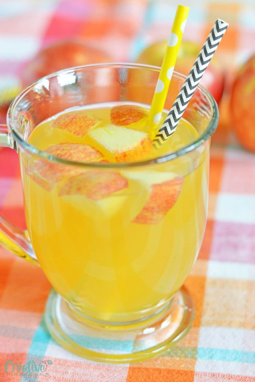 Image of alcoholic apple cider in a mug, decorated with apples and paper straws