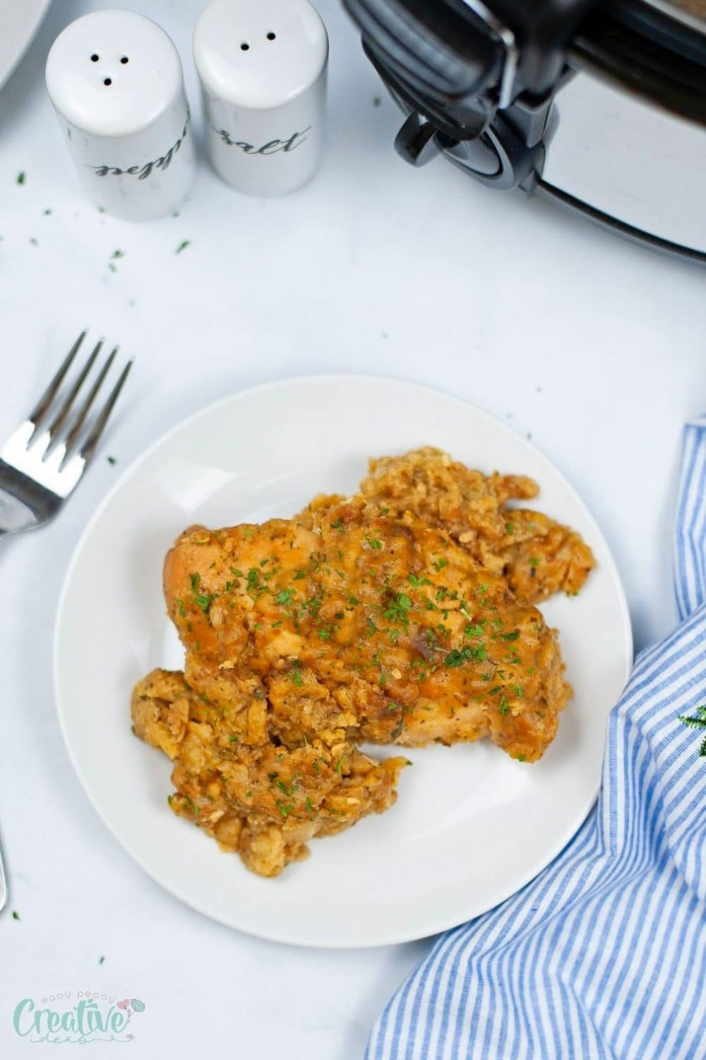 Image of chicken stuffing casserole on a white plate next to the slow cooker where it was cooked