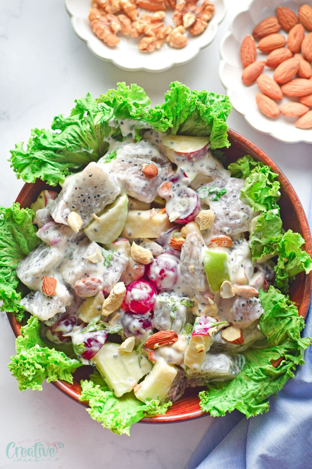 Top view of a brown salad bowl filled with dragon fruit salad made in the Waldorf salad style