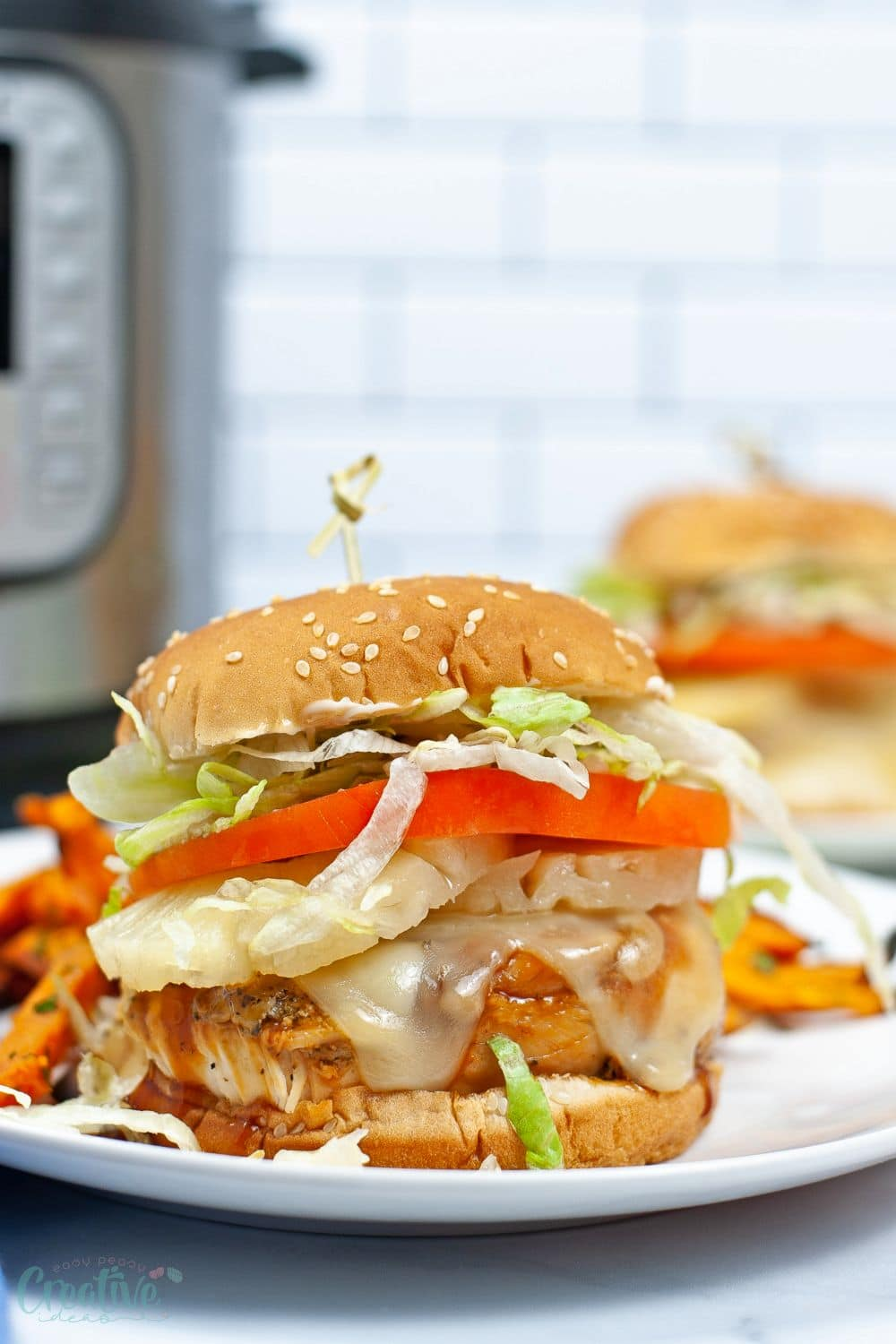 Close up image of Instant Pot chicken teriyaki served in a burger bun with lettuce and cheese