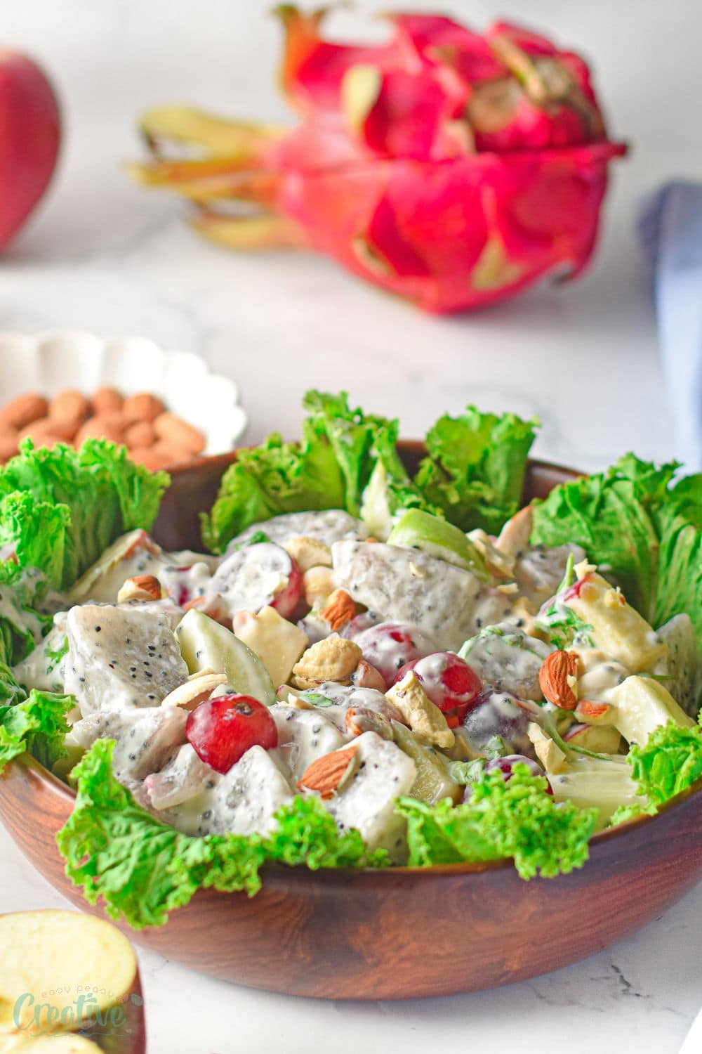Close up image of modern Waldorf salad prepared with dragon fruit and displayed on a bed of lettuce, in a brown salad bowl