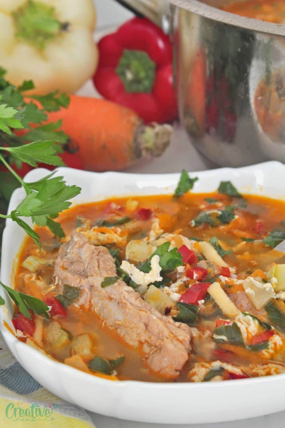 Image of pork vegetable soup made with spare ribs, fresh vegetables and noodles, served in a white soup bowl