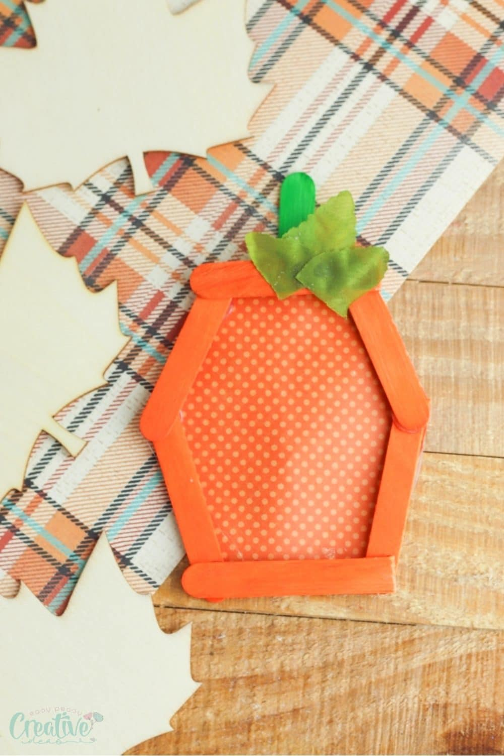 Image of pumpkin craft for kids made with popsicle sticks and paper