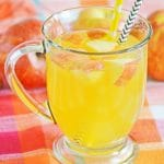 Spiked apple cider in a mug, decorated with apples and paper straws