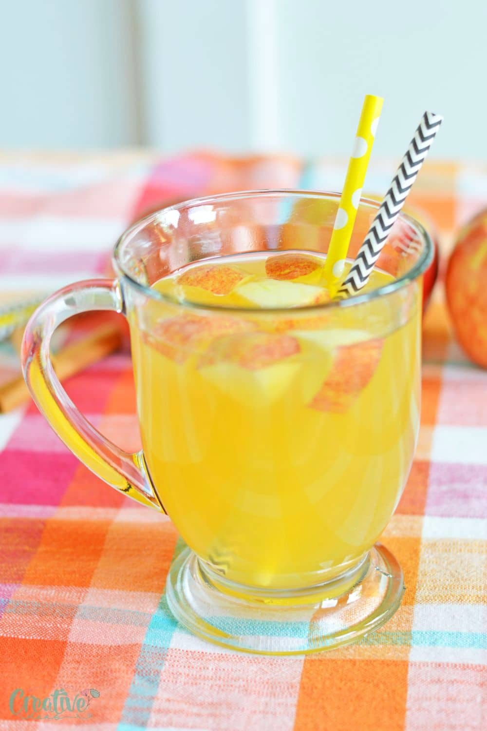Close up image of spiked caramel apple cider in a drinking mug, decorated with apples and paper straws