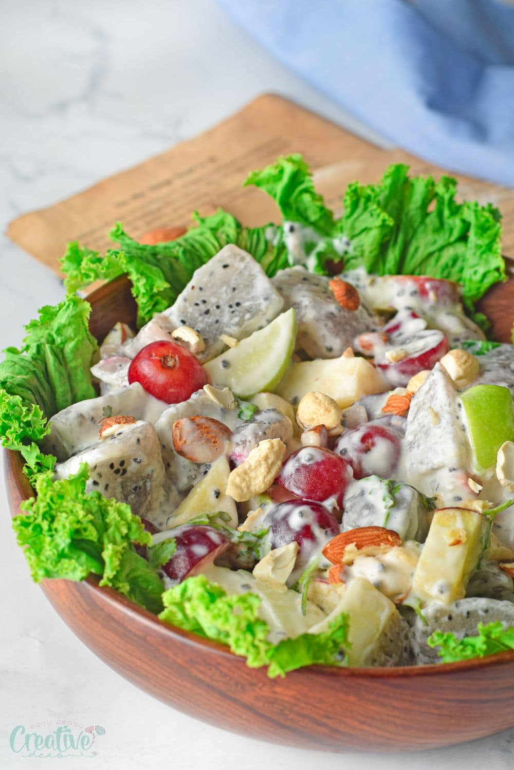 Close up image of Waldorf salad ingredients on a lettuce bed, in a brown salad bowl